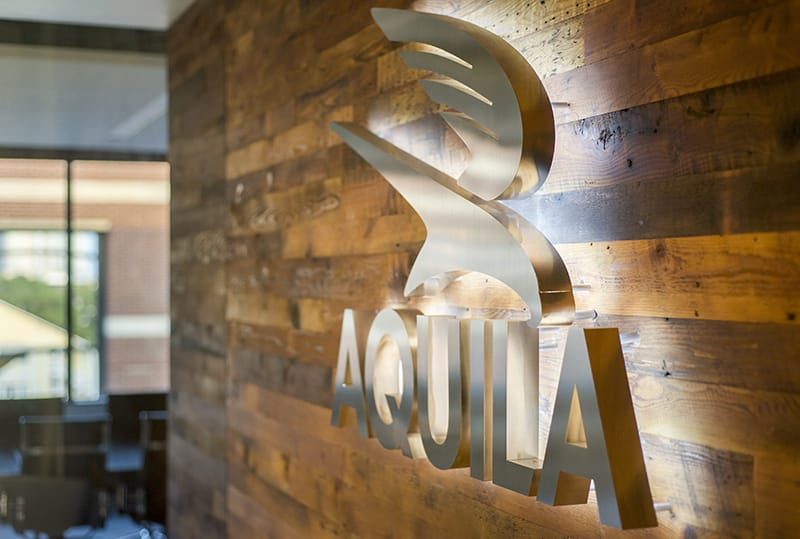 A detail photo of Aquila Commercial's lit sign on the wall of their office