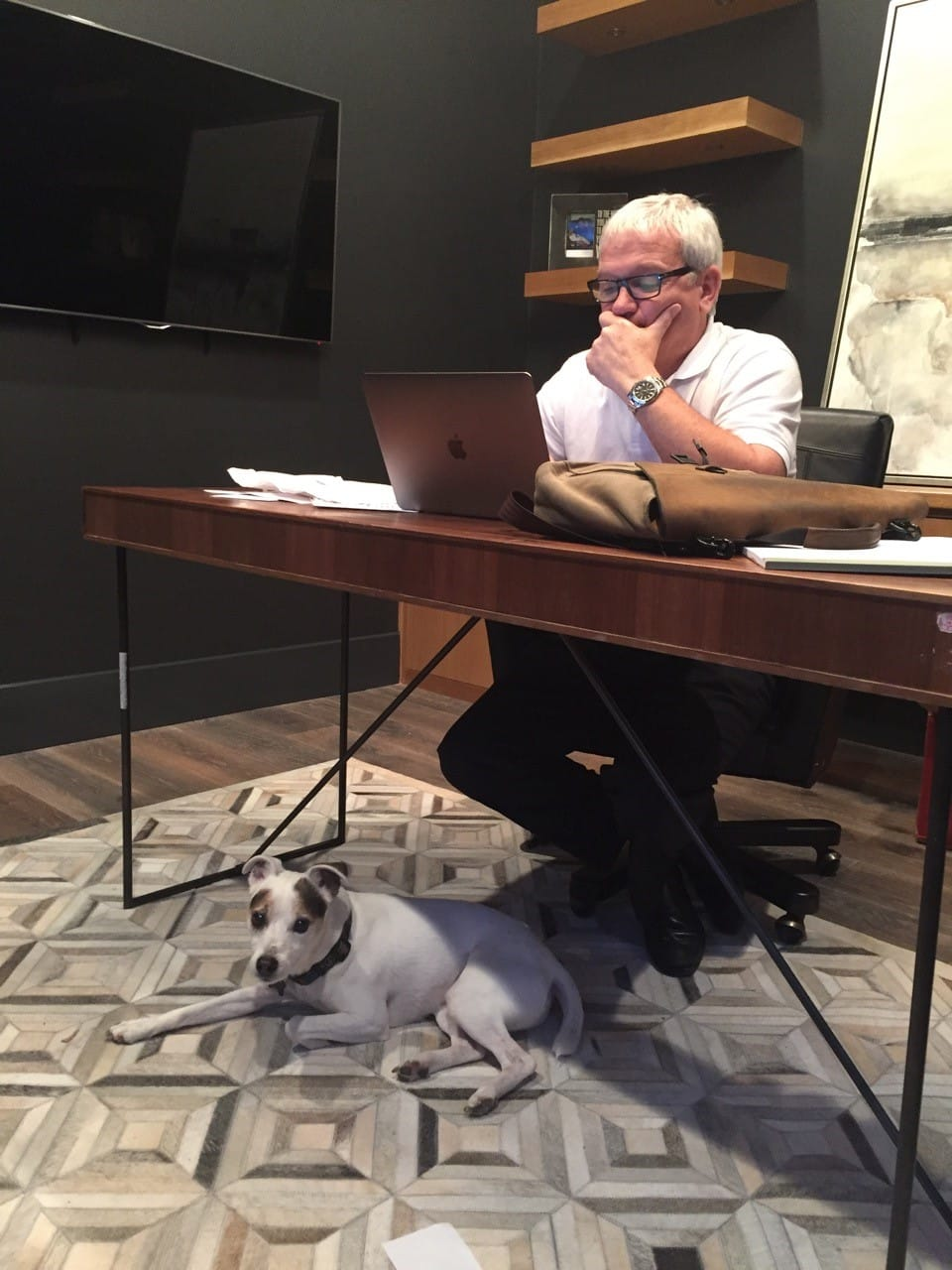 Mike with his dog in his home office.